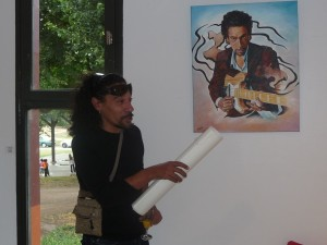 Chyco Simeon near his painting.